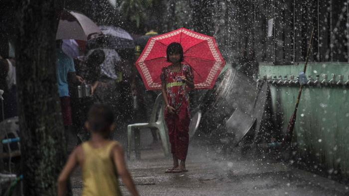 TOPSHOT - A girl shields herself from the rain with an umbrella as it rains in Yangon on May 30, 2017. Tropical Cyclone Mora, which formed in the Bay of Bengal, is expected to hit Bangladesh, Northeast India and western Myanmar with strong winds and heavy rains. / AFP PHOTO / YE AUNG THUYE AUNG THU/AFP/Getty Images
