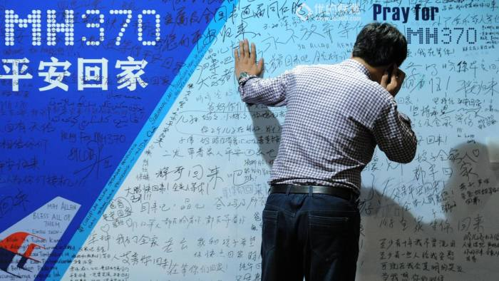 A man uses a mobile phone while looking at a billboard in supportof missing Malaysia Airlines flight MH370 as relatives attend a meeting with delegates from Malaysia at the Metro Park Lido Hotel in Beijing on March 30, 2014.  Almost 30 relatives of Chinese passengers on the missing Malaysia Airlines flight arrived on March 30 in Kuala Lumpur to demand answers about the plane's fate, with some calling for an apology from Malaysia's government.    AFP PHOTO / WANG ZHAO        (Photo credit should read WANG ZHAO/AFP/Getty Images)