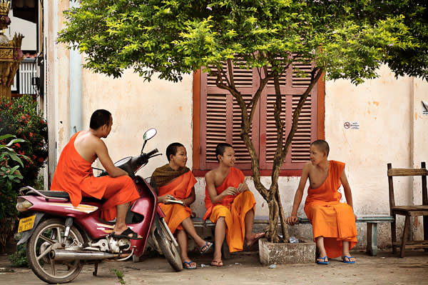 Buddhist monks sitting in front of a French colonial villa in Vientiane