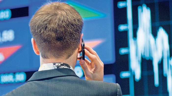 A trader views speaks on a mobile phone on the main trading floor of the Warsaw Stock Exchange in Warsaw, Poland, on Tuesday, May 24, 2011