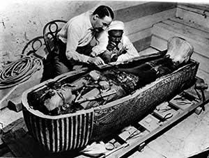 Howard Carter examining Tutankhamun's casket