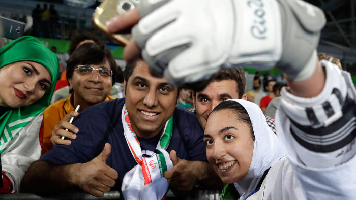 Kimia Alizadeh Zenoorin of Iran takes a selfie photo with spectators as she celebrates after winning the bronze medal in a women's Taekwondo 57-kgcompetition at the 2016 Summer Olympics in Rio de Janeiro, Brazil, Thursday, Aug. 18, 2016. (AP Photo/Andrew Medichini)
