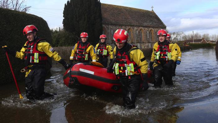 MOORLAND, UNITED KINGDOM - FEBRUARY 19: Police officers in drysuits use a boat to patrol the flooded and largely evacuated village of Moorland on the Somerset Levels on February 19, 2014 in Somerset, England. As the flood water finally appears to be stabilising many people are only just beginning to count the true cost of the recent flooding. (Photo by Matt Cardy/Getty Images)