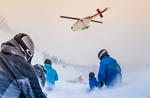 Skiers waiting for a Bell 212 to pick them up