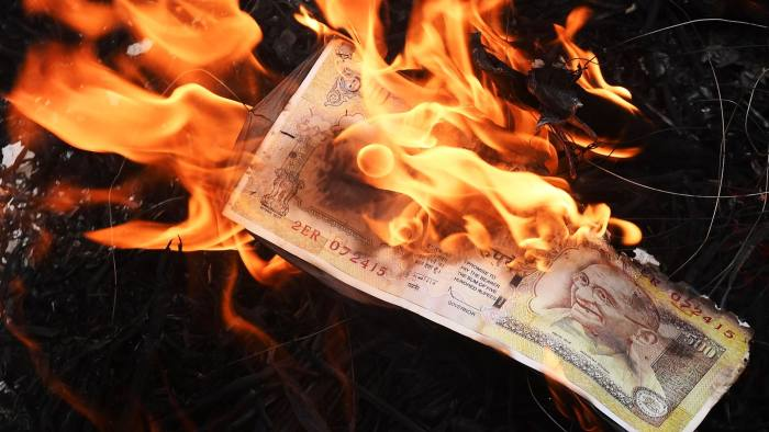 Leftist activists burn a poster of a 500 rupee notes during a protest rally against Indian prime minister Narendra Modi in Kolkata on November 14, 2016. Prime Minister Narendra Modi on November 14, urged Indians to give him more time to resolve a cash crunch that followed the withdrawal of high-value banknotes from circulation, as rival politicians lashed out at his handling of the crisis. / AFP PHOTO / Dibyangshu SARKARDIBYANGSHU SARKAR/AFP/Getty Images