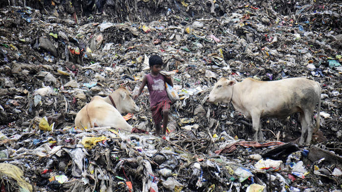An Indian rag-picker looks for recyclable material in what is reportedly the largest rubbish tip in the state of Assam on the eve of World Environment Day in the Boragoan area of Guwahati on June 4, 2015