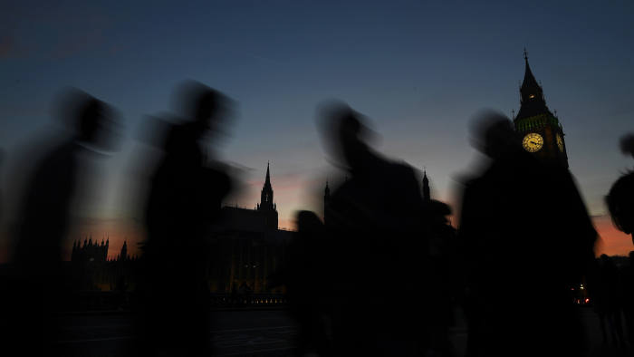 People cross Westminster Bridge as dusk falls behind the Houses of Parliament on a clear evening in central London, Britain December 5, 2016.  REUTERS/Toby Melville