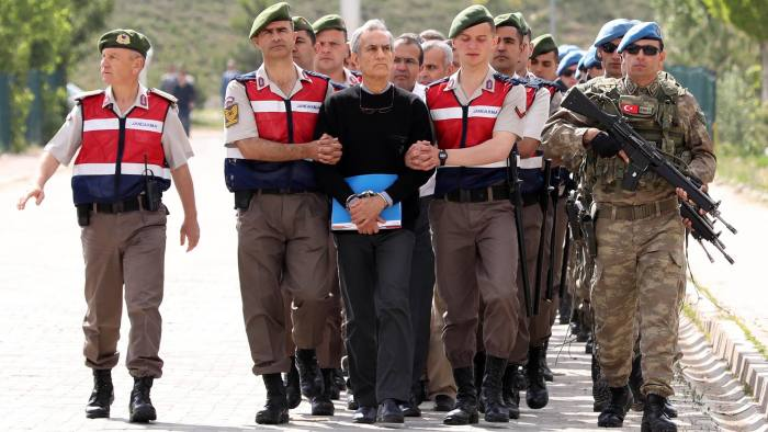 TOPSHOT - Turkish Gendarmerie escort defendants Akin Ozturk (3L) and others involved in last Julys attempted coup in Turkey as they leave the prison where they are being held, ahead of their trial in Ankara, on May 22, 2017. The trial opened on May 22, 2017 of more than 220 suspects, including over two dozen former Turkish generals, accused of being among the ringleaders of the attempted coup last year aimed at ousting President Recep Tayyip Erdogan. / AFP PHOTO / ADEM ALTANADEM ALTAN/AFP/Getty Images