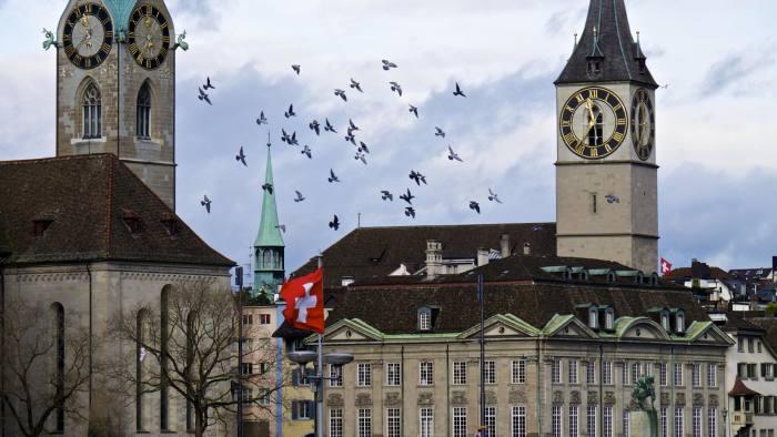 A Swiss national flag flies between the spires of Fraumeunster church and St Peter's Church in Zurich, Switzerland