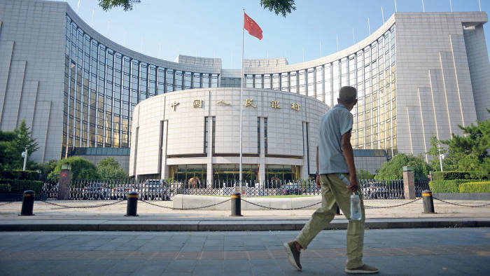 An elderly man walks past The People's Bank of China in Beijing on August 12, 2015
