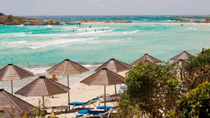 Wooden umbrellas with sunbed on the beach in Cyprus pfeatures