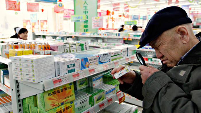 An elderly man uses a magnifier to see the descriptions on a pack of medicine at a pharmacy in Dandong
