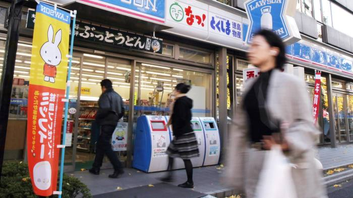 A pedestrian walks past a Lawson Inc. convenience store in Tokyo, Japan, on Monday, Dec. 21, 2009. Lawson Inc. is Japan's second-largest convenience store operator. Photographer: Tomohiro Ohsumi/Bloomberg