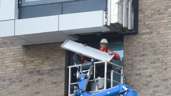 Workers remove panels of external cladding from the facade of a building in the Wythenshawe area of Manchester, northwest England, on June 25, 2017. The Wythenshawe Community Housing Group (WCHG) which run the development the building is part of took the decision, announced in a June 22 statement, to remove 78 feature panels of external cladding from the development after fire safety tests in the wake of the Grenfell Tower fire. Some 34 high-rise buildings in 17 local authorities in England have already failed urgent fire tests conducted after Grenfell, the government announced June 24, raising fears that thousands more may need to leave their homes. / AFP PHOTO / PAUL ELLISPAUL ELLIS/AFP/Getty Images