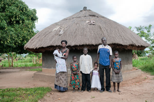 The family of Bosco and Eunice photographed outside their home near Gulu in Uganda