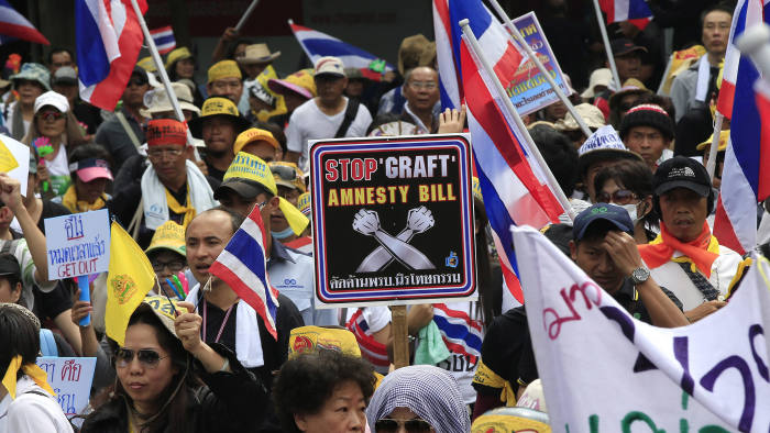 Thai protestors march through the streets holding Thai flags as they try to reach Thai Government House to demonstrate against a controversial amnesty bill, in Bangkok