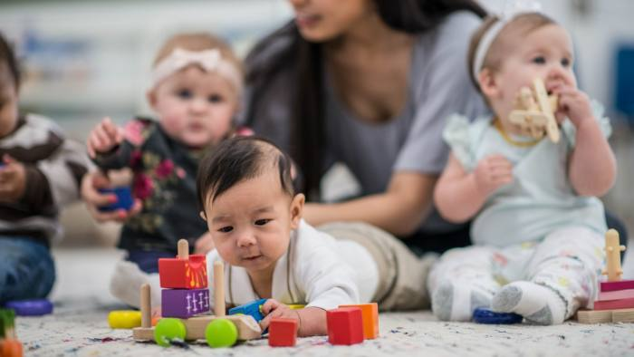 A multi-ethnic group of babies are indoors in a daycare center. They are wearing casual clothing. They are playing with toys along with their babysitter. One baby is crawling on the floor and playing with a car in the foreground.