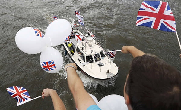 People wave balloons and and flags as a flotilla of fishing vessels campaigning to leave the European Union sail up the river Thames in London, Britain June 15, 2016. REUTERS/Stefan Wermuth