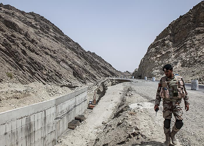 A member of the security forces observes ongoing construction at the M8 motorway on the outskirts of Gwadar, Balochistan, Pakistan, on Wednesday, Aug. 3, 2016. Gwadar is the cornerstone of Chinese President Xi Jinping's so-called One Belt, One Road project to rebuild the ancient Silk Road, a trading route connecting China to the Arabian Sea that slices through the Himalayas and crosses deserts and disputed territory to reach this ancient fishing port, about 500 miles by boat from Dubai. Photographer: Asim Hafeez/Bloomberg