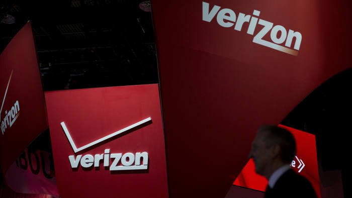 An attendee walks past the Verizon Communications Inc. booth during the 2015 North American International Auto Show (NAIAS) in Detroit, Michigan, U.S., on Tuesday, Jan. 13, 2015. NAIAS will reveal approximately 40-50 global and North American vehicles during the Jan. 12-13 press preview for the show. Photographer: Andrew Harrer/Bloomberg