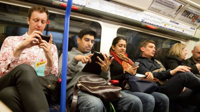 CT00GR Passengers using mobile phones, iPads and computer game technology on a london underground train, UK