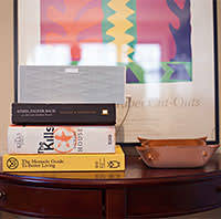 A stack of books sits in front of a poster of a Henri Matisse paper cutout in home of 24 year old Codecademy founder Zach Sims. New York City