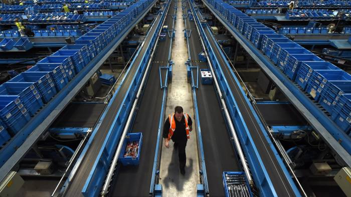 A worker walks alongside a conveyor belt as items are sorted into crates to be sent to retail stores from the Argos Distribution Centre in Burton-upon-Trent, central England, on November 27, 2015.