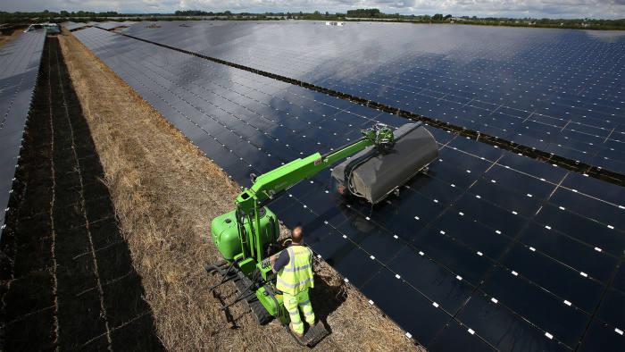 A workman uses a machine to clean panels at Landmead solar farm on July 29, 2015 near Abingdon, England
