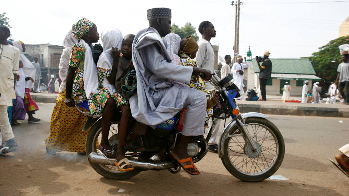 A man leaves with his children on a motocycle after attending the Eid al-Fitr prayers at Kofa Mata praying ground, to mark the end of holy month of Ramadan, in Nigeria's northern city of Kano, July 6, 2016.REUTERS/Akintunde Akinleye - RTX2JYIO