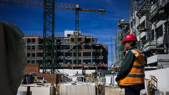A worker operates a crane using a remote device on a residential construction site operated by Neinor Homes S.L.U. in the San Sebastian de los Reyes district of Madrid, Spain, on Wednesday, March 8, 2017