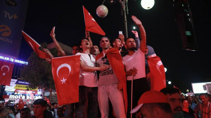 People wave flags as they gather in Kizilay Square in Ankara on July 16, 2016 during a demonstration in support to the Turkish president. President Recep Tayyip Erdogan battled to regain control over Turkey on July 16, 2016 after a coup that claimed more than 250 lives, bid by discontented soldiers, as signs grew that the most serious challenge to his 13 years of dominant rule was faltering.