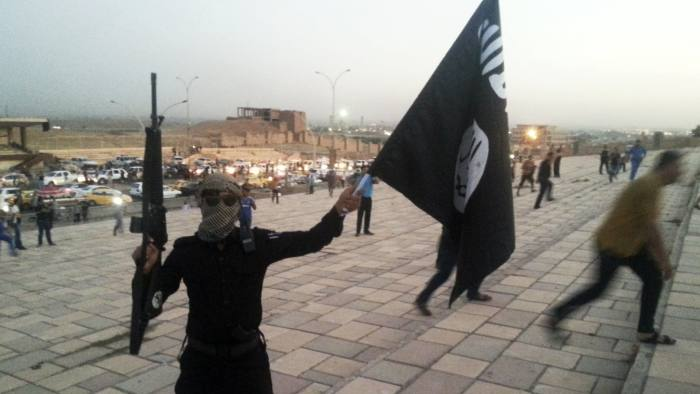 A fighter of the Islamic State of Iraq and the Levant (ISIL) holds an ISIL flag and a weapon on a street in the city of Mosul, June 23, 2014. U.S. Secretary of State John Kerry held crisis talks with leaders of Iraq's autonomous Kurdish region on Tuesday urging them to stand with Baghdad in the face of a Sunni insurgent onslaught that threatens to dismember the country. Picture taken June 23, 2014. REUTERS/Stringer (IRAQ - Tags: CIVIL UNREST POLITICS TPX IMAGES OF THE DAY) - RTR3VIB1