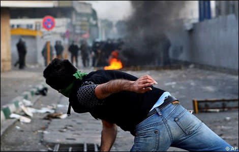 A protester recoils after throwing a projectile at Iranian riot police in Tehran