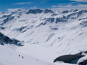Skiers descending towards Lac de Moiry