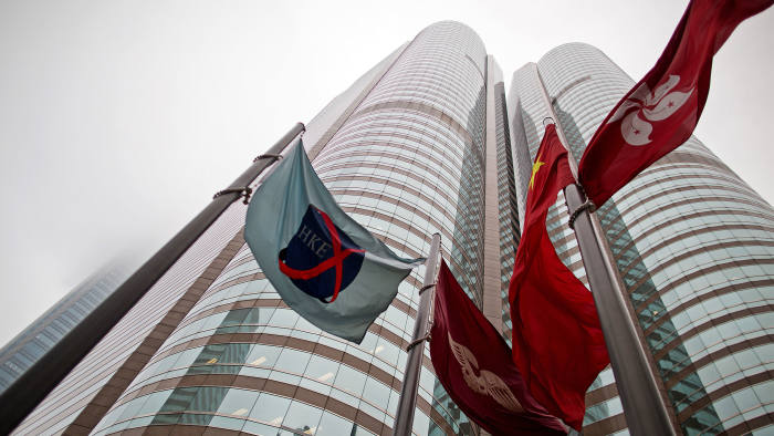 The flag of the Hong Kong Exchanges and Clearing Ltd. (HKEx), left, flies from a mast outside the Stock Exchange buildings in Hong Kong, China