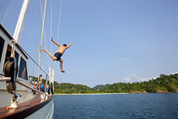 A man jumps off the Meta IV yacth and into the waters of the Mergui archipelago