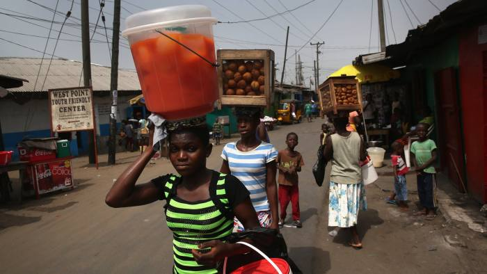 MONROVIA, LIBERIA - FEBRUARY 09: Women walk with their wares through the West Point slum on February 9, 2016 in Monrovia, Liberia. West Point, the most impoverished and overpopulated community in Liberia, was hard hit by the Ebola outbreak, and health facilities at the time were overwhelmed. After almost two years, on January 14, 2016 the World Health Organization declared the epidemic over, after the virus had killed some 11,300 people and infected more than 28,500 people in West Africa. (Photo by John Moore/Getty Images)