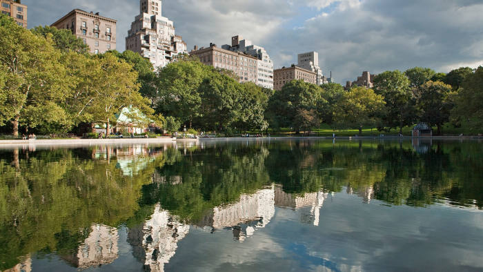 Fifth Avenue apartment buildings reflected in Central Park's Conservatory Water
