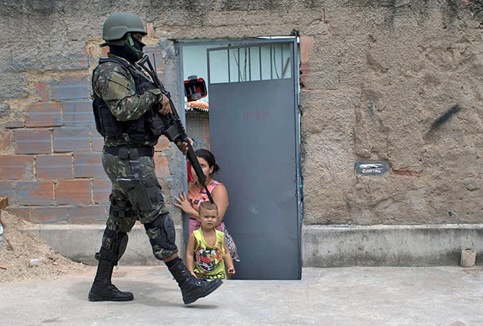 TOPSHOT - A Brazilian army soldier walks past a child, during a security operation at Barbante favela, where earlier in the week alleged drug traffickers destroyed a police post in Rio de Janeiro, Brazil on November 30, 2017. / AFP PHOTO / LEO CORREALEO CORREA/AFP/Getty Images