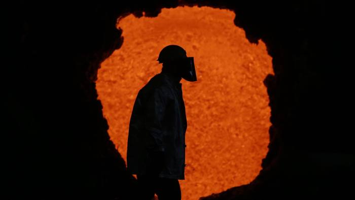 Steel Manufacture At ArcelorMittal's Bosnia Plant...A worker dressed in heat protective clothing passes red hot metal in a furnace at the ArcelorMittal steel plant in Zenica, Bosnia, on Thursday, March 17 2016. Steel has become a flash point in EU-China trade relations as Chinese producers challenge European manufacturers such as ArcelorMittal and ThyssenKrupp AG by shipping excess supply to Europe. Photographer: Oliver Bunic/Bloomberg