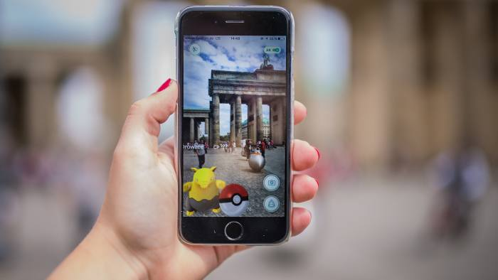 A woman points her smart phone at the Brandenburg Gate as she plays the Pokemon Go mobile game in Berlin on July 13, 2016. The Pokemon Go mobile gaming craze reached European fans with players in Germany the first to get their hands on the augmented reality sensation. / AFP / dpa / Sophia Kembowski / Germany OUT (Photo credit should read SOPHIA KEMBOWSKI/AFP/Getty Images)