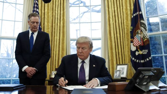 President Donald Trump, joined by U.S. Trade Representative Robert Lighthizer, left, signs Section 201 actions in the Oval Office of the White House in Washington, Tuesday, Jan. 23, 2018. Trump says he is imposing new tariffs to
