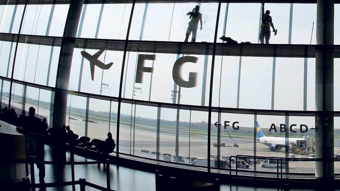 Workers clean the windows in the departure area at Vienna's airport in Schwechat April 2, 2014