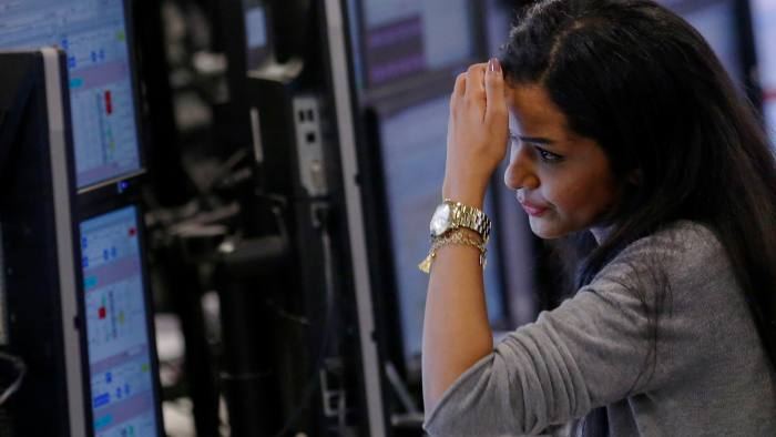 A trader looks at financial data on computer screens