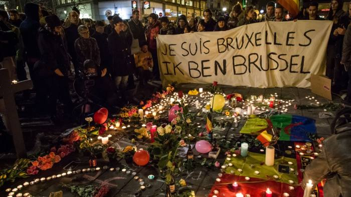 "People hold a banner reading in French and Flamish ""I AM BRUSSELS"" as they gather around floral tributes, candles, belgian and peace flags and notes in front of the Bourse of Brussels on March 22, 2016 in tribute to the victims of Brussels following triple bomb attacks in the Belgian capital that killed about 35 people and left more than 200 people wounded. Belgium launched a huge manhunt on March 22 after a series of bombings claimed by the Islamic State group ripped through Brussels airport and a metro train, killing around 35 people in the latest attack to bring carnage to the heart of Europe. / AFP PHOTO / BELGA AND Belga / Aurore Belot / Belgium OUTAURORE BELOT/AFP/Getty Images"