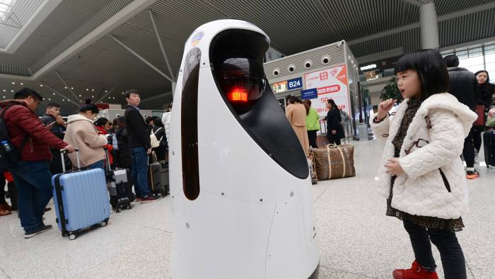 ZHENGZHOU, CHINA - FEBRUARY 15: A police robot patrols at Zhengzhou East Railway Station on February 15, 2017 in Zhengzhou, Henan Province of China. The police robot can do the cleaning, monitor the air quality, find fire and can also recognize passengers' faces to compare with the faces of the escaped criminals. (Photo by Zhang Tao/VCG via Getty Images)