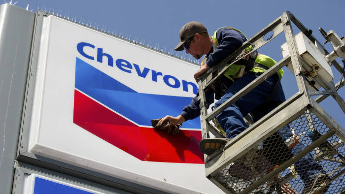 Employee Brandon Scully works on a Chevron Corp. sign at a gasoline station in San Francisco, California