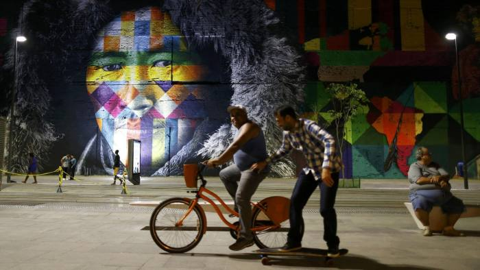 Locals walk past a mural created by Brazilian artist Eduardo Kobra that covers nearly 3,000 square meters of wall space Rio de Janeiro