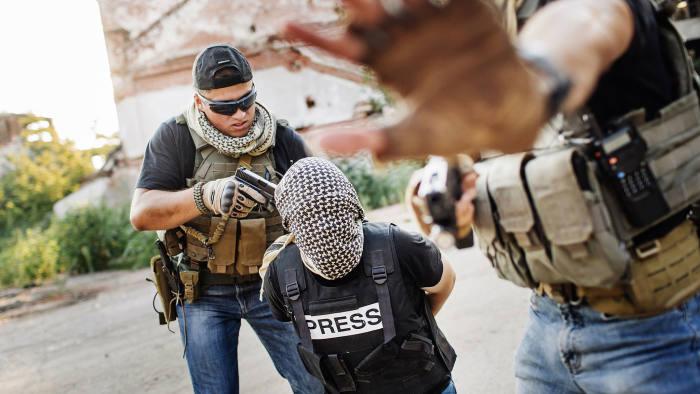 terrorists-holding-gun-to-journalist-head-photo