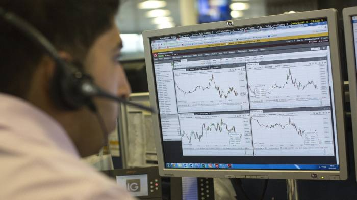 A dealer looks at financial data on computer screens on the trading floor of IG Group Holdings Plc in London, U.K., on Tuesday, July, 21, 2015. IG Group Holdings Plc fell the most in more than six months after the spread-betting firm reported a 13 percent drop in full-year profit, hurt by the Swiss National Bank's surprise decision in January to scrap a currency cap. Photographer: Simon Dawson/Bloomberg